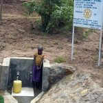 Flicka hämtar vatten vid Kumerukällan.